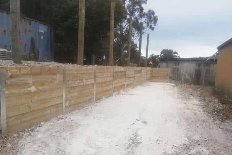 An image of a Ballarat backyard with a newly built high retaining wall holding in mulch and trees